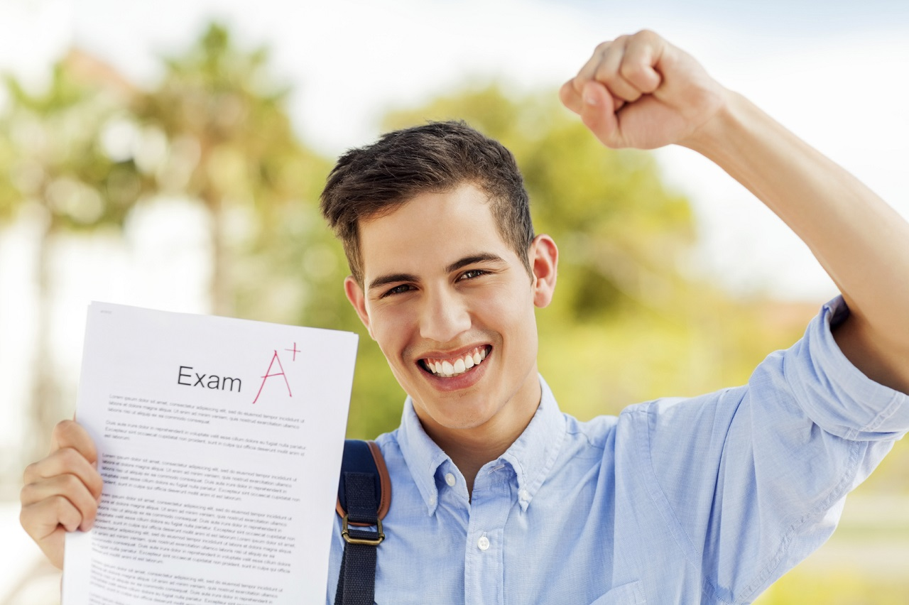 Portrait of successful boy clenching fist while showing test result with A+ grade on college campus. Horizontal shot.